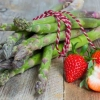 Green asparagus with strawberries on wooden